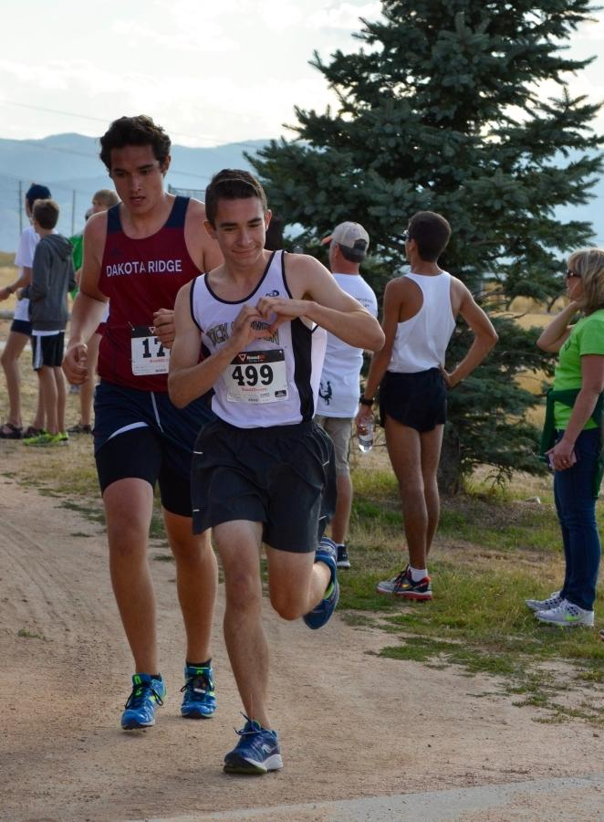 David Florez '17 signals to watching fans as he competes in the JV race of Rock Canyon's first cross country meet at Mountain Vista, August 26th.