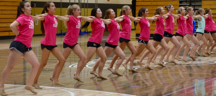 Sat.+Oct.+8%2C+members+of+the+Varsity+Poms+team+gather+in+the+main+gym+to+perform+a+kickline+as+a+part+of+their+most+recent+dance.