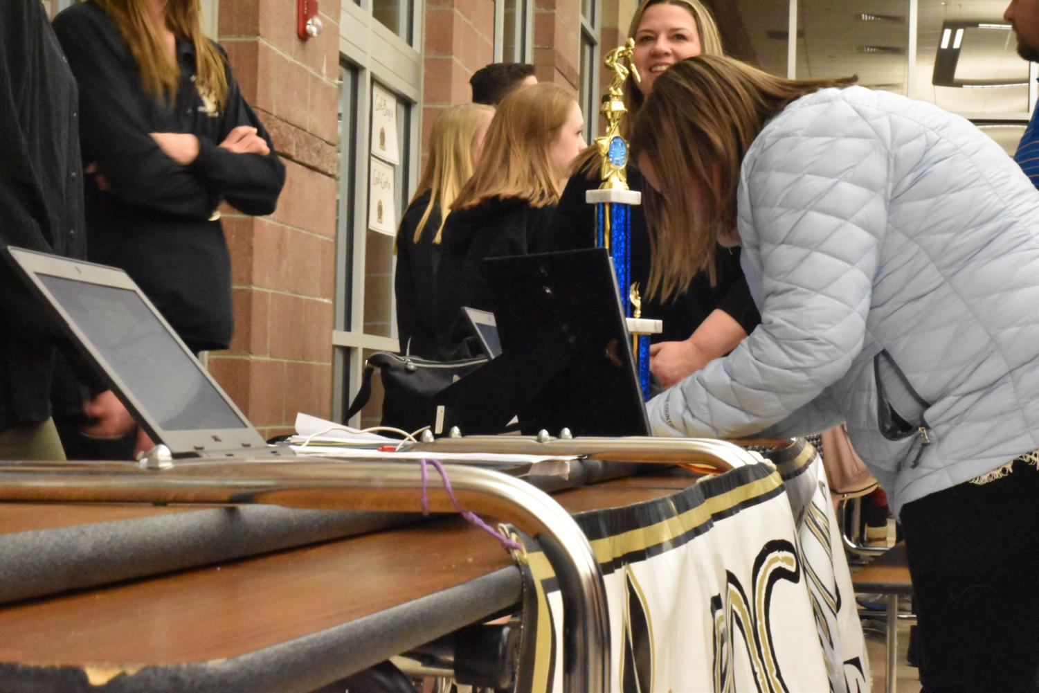 Middle school students and their parents fill out information sheets at the Swim and Dive table during the Rock Canyon 8th Grade Information Night, Wed., Jan. 24.  Students interested in attending the school next year took part in the event to learn about the various clubs and activities that the school offers.  Current high schoolers set up tables at which they aided the prospective students in deciding which activities would be best for them.