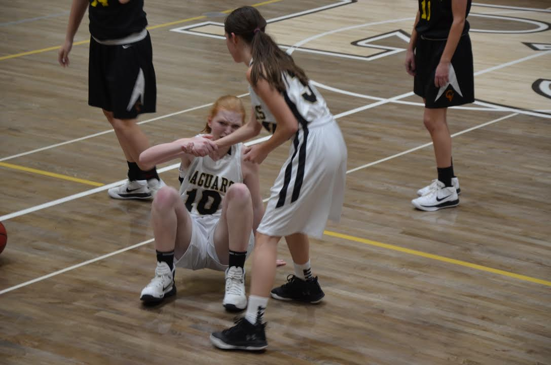 Guard Rebecca Lindsay '21 grabs point guard, Josie Gibson's '21, outstretched hand to help her up during  girls c-team basketball game, Tuesday, Feb. 13.