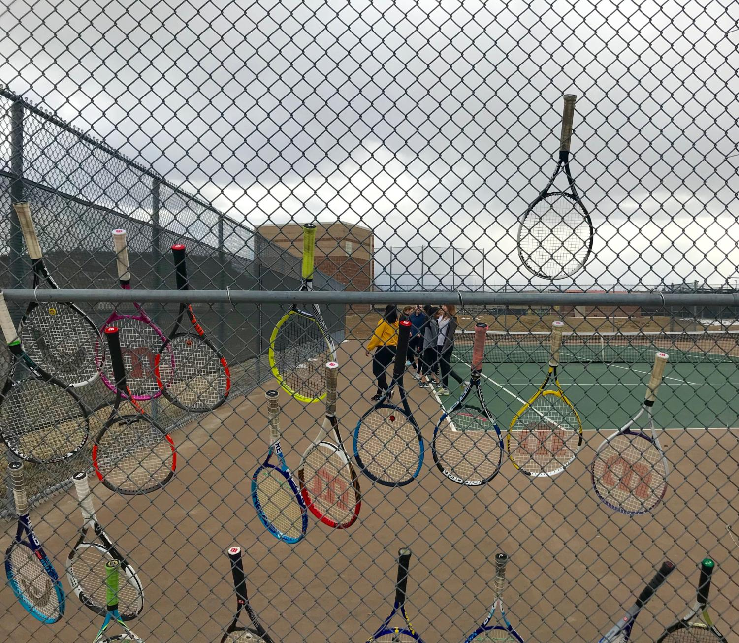 Tennis players hang their rackets on the fence during practice.