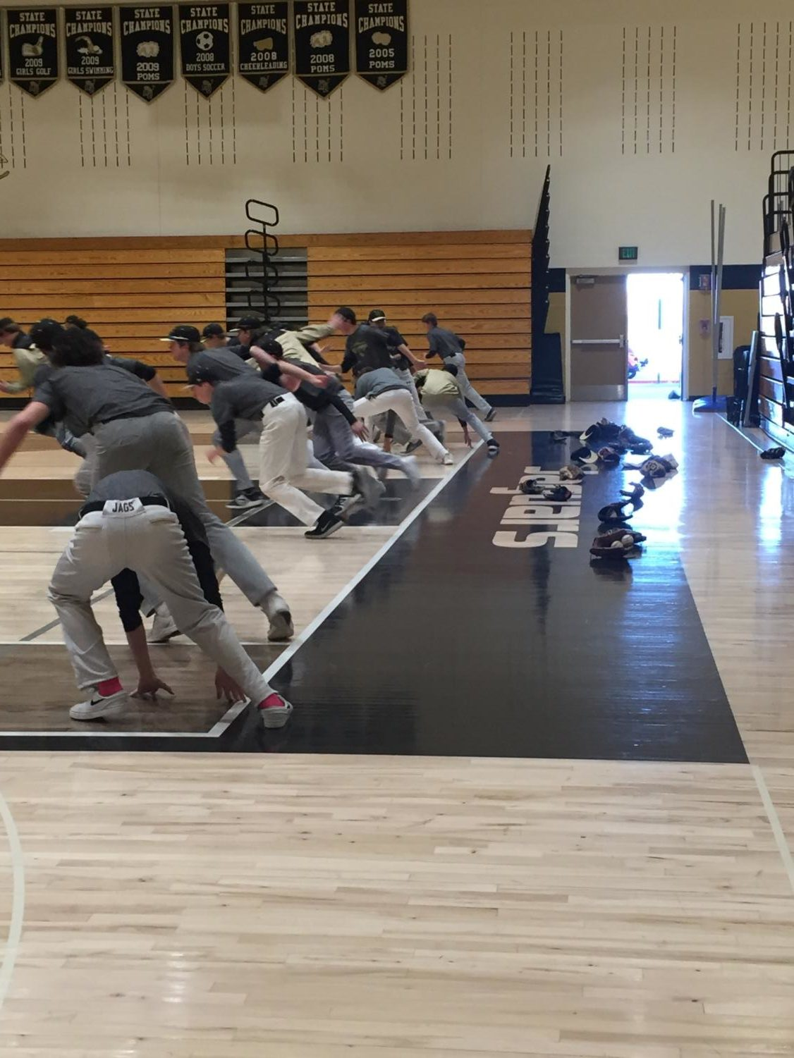 The boys baseball players reach down to touch the baseline for another sprint in the main gym during practice, Monday, Mar. 5.  The boys baseball practice had been moved inside due to strong winds and cold temperatures outdoors.
