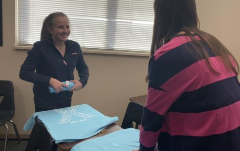 Sophomores Emma Renard and Hailey Poppler fold shirts to be packaged for Wish Kit sales. Student Council ordered about 2,600 shirts so the whole student body has a chance to buy a shirt.