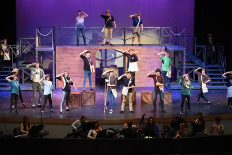 "The cast of Newsies rehearses after school in the auditorium Feb. 20. The cast, crew, and pit members have been working since the end of December to put the production together. ""I play the part of Joseph Pulitzer and it's fun being a part of a family."" Lily Schmoker"