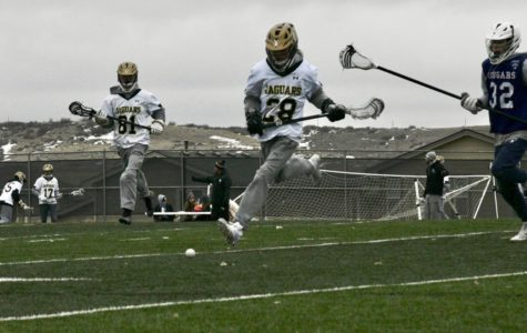 JV boys lacrosse player Ryan Grafitti '22 runs to the ball to beat his defender in the second half of the Cherokee Trail scrimmage on the turf field March 2. As part of fundraiser for their teams, the boys sold tickets for ten dollars each for the sandwich food truck during the scrimmages.