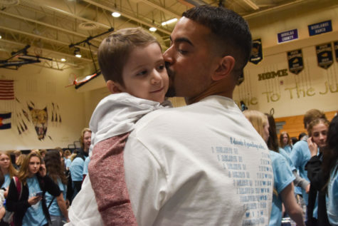 "Michael McGuire lifts and kisses his son, Wish Kid Michael McGuire during the closing assembly in the gym March 8. The closing assembly celebrated Michael and his wish to go to Disney World. ""I think Michael was my favorite part about Wish Week. My favorite part was when he stole the microphone at the opening assembly. I think he"
