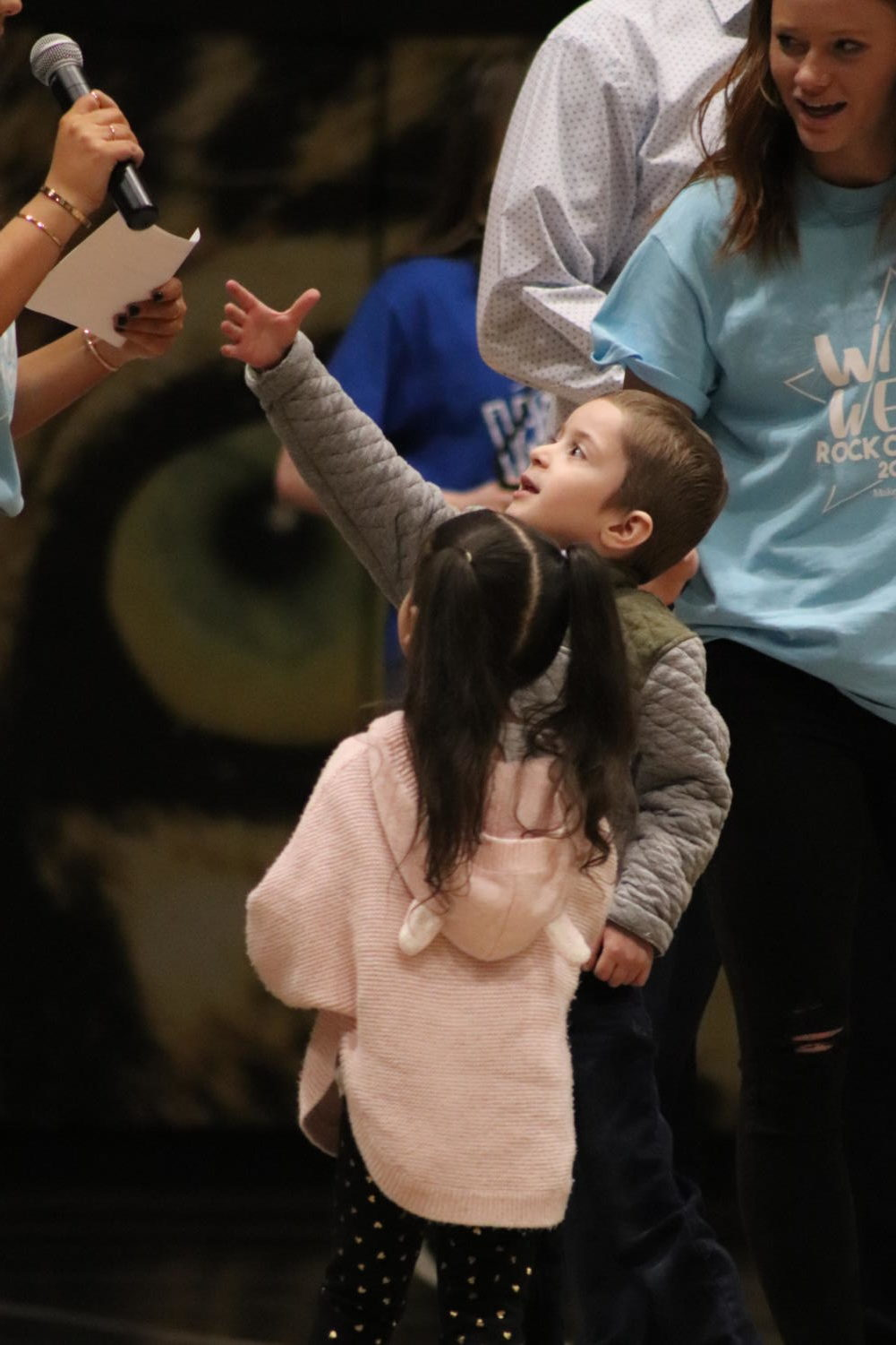 Five year old Michael, diagnosed with leukemia reaches for the microphone to share some words of wisdom during the Wish Week opening Assembly in the gym March 1. Michael wished to go to Disney World to meet Mickey and Minnie Mouse.