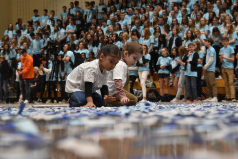 Wish Kid Michael McGuire and his sister, Genevieve McGuire, play in the confetti on the gym floor during the closing assembly March 8. The two spent the rest of the assembly romping in the confetti Student Council dispersed throughout the gym.
