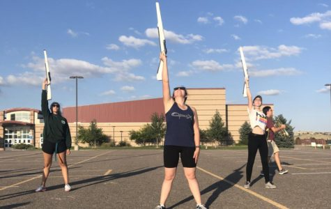 Anitra Dolan '20, Morgan Williams  '20, and color guard instructor Marguerite Buhr practice a new routine after practice in the upper parking lot Aug. 27. This was the first night the color guard section learned rifle work for movement three.