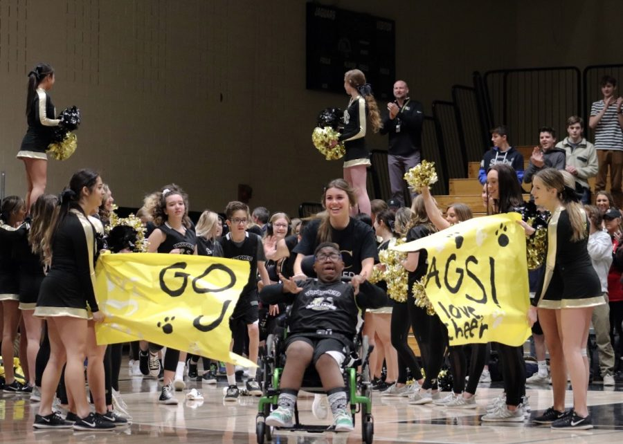 "David O'Keefe '23 bursts through the ""Go Jags!"" banner in the gym during his team's introduction at the First Annual Unified Basketball Game Jan. 22. In the past, the Unified Basketball team's basketball hoops were trash cans, but their equipment was upgraded with adapted basketball hoops for optimum accessibility for all students. ""We're trying to change the culture of Unified Basketball. Every day, it's a challenge for them to be heard, to be respected and to compete in sports, but they push themselves every day past all those challenges,"" Unified Basketball Coach Jerome Price said."