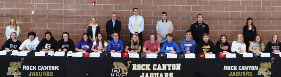 Student+Athletes+get+ready+to+sign+their+letter+of+intent+with+their+coaches+standing+behind+them.