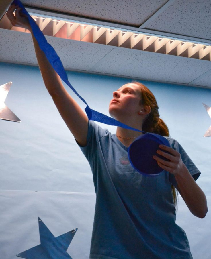 Caroline Pita '21 helps decorate the 9000s pod by hanging streamers Feb. 20. The pod was themed blue, for Wish Week.