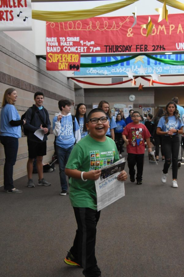 Fabian laughs while holding a copy of the Rock in the main hallway Feb. 21. Student Council took Fabian and his family on a tour of the school after the Opening Assembly to show off the decorations.