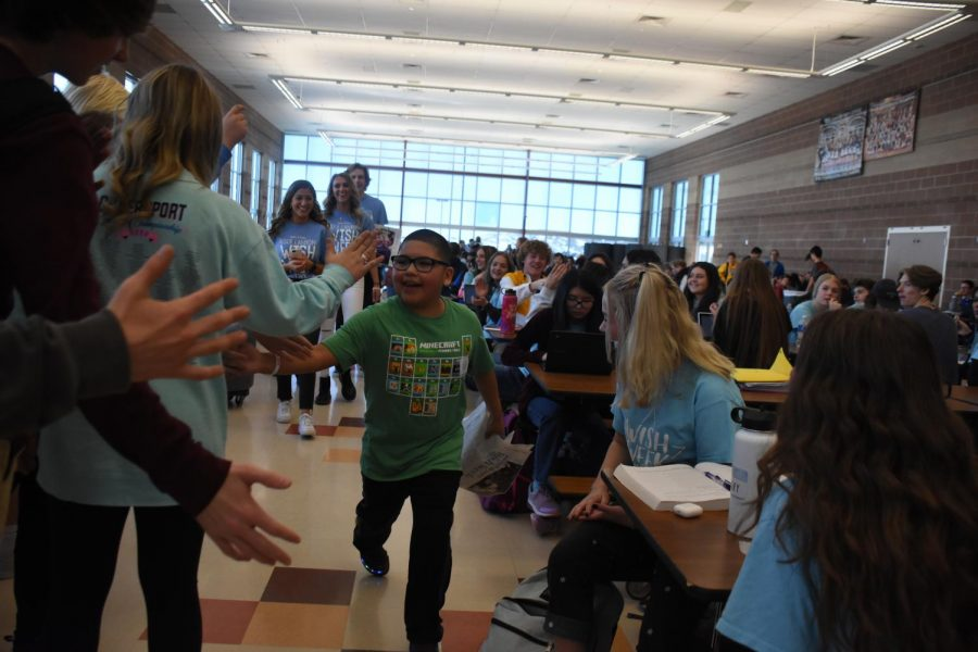 Fabian high fives students in the lunchroom during Access Feb. 21. Fabian wished to go to LEGOLAND.