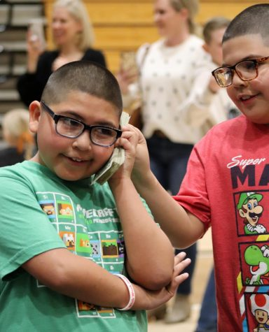 Fabian and his brother, Martin play with a stack of dollar bills collected during the Miracle Minute Feb. 21. Fabian's brother engaged with him throughout the opening assembly, both expressed their excitement as family watched on.