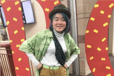 Chloe Nowak '22 flaunts her tacky wear in from of the RC Wish Week stand Feb. 25. Nowak wore a fedora, a turtle neck with a lime green Hawaiian shirt over it, a fanny pack, khaki shorts with a lime green belt, leggings, and socks with lime green sandals.
