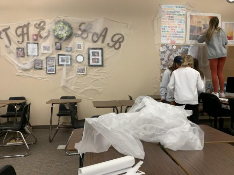 Yearbook students cover wall decorations in room 4113, to prepare for the cleaning over spring break March 13. After announcing a two-week school closure, the district also announced that schools would be sprayed down over spring break with industrial chemicals, to counter the coronavirus.