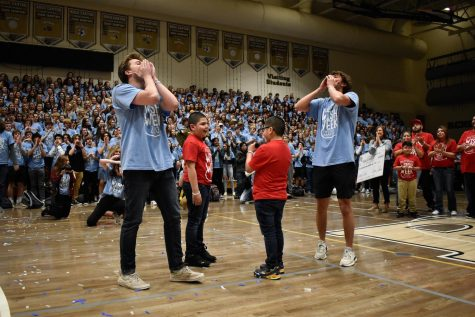 "Golden boys Dani Haddad and Cody Lange '20, along with Wish Kid Fabian and his brother Carlos, lead the student body in chanting, ""I believe in Fabian's wish,"" at the closing assembly Feb. 28. Fabian joined in leading the chant after student council presented the Make A Wish Foundation with the money raised throughout the week."
