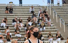 Varsity cheerleader Izzy Harris '24 waits on the sidelines in front of a socially-distanced crowd Oct. 8. This was the first football game of the season for the entire state. Columbine won  39-13.