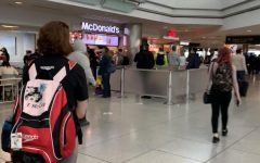 In Gate C, there are multiple fast food restaurants open such as McDonald's Dec. 10th. Passengers waited in line and ordered food while waiting for their flight.
