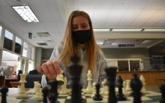 """Wendy Werner '22 places the knight on space F3 in a chess game in the Learning Commons March 3. The Chess Club met for their first meeting of the year after going full remote. """"I've always enjoyed this games for all the challenges it provides and fun atmosphere,"""" Werner said."""