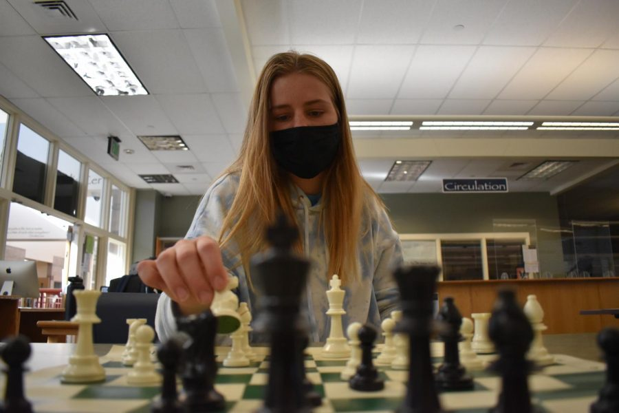 "Wendy Werner '22 places the knight on space F3 in a chess game in the Learning Commons March 3. The Chess Club met for their first meeting of the year after going full remote. ""I've always enjoyed this games for all the challenges it provides and fun atmosphere,"" Werner said."