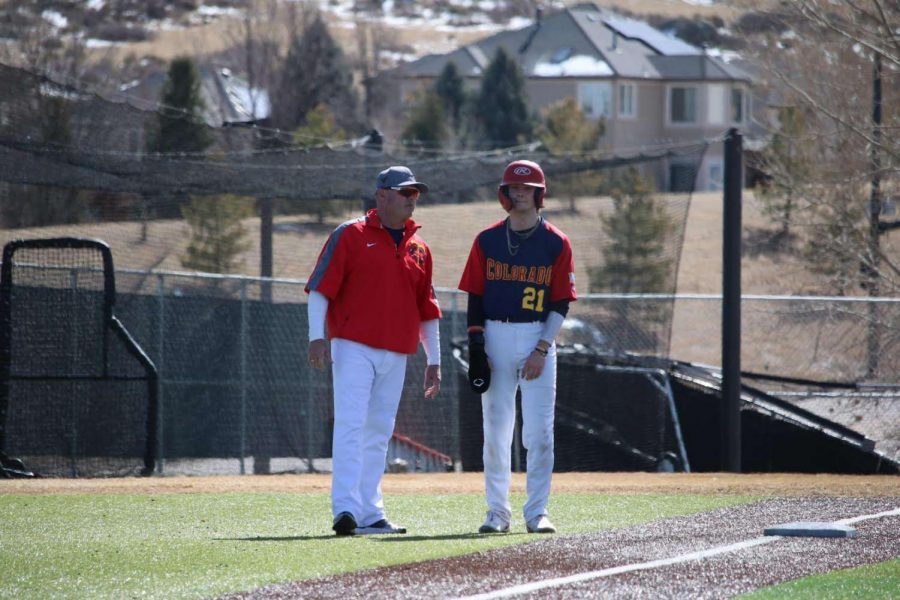 Brayden Duman '23 converses with assistant coach Dean Adams at third base after hitting a triple during a Spring Training Game.
