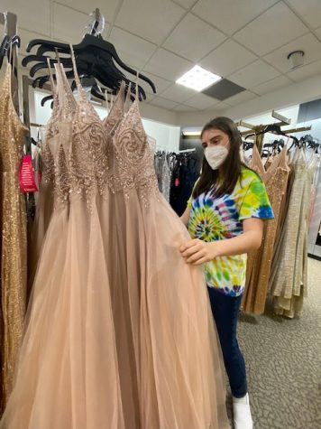 "Ava Schneiderman '21 looks for a prom dress at Dillard's April 21. Despite the location of Main Event, the student council has decided to keep traditional and formal attire for the event. ""I'm glad that it's still happening. Sometimes dress shopping is a bit of a hassle, but it's nice to get to dressed up for a night because you don't really get to wear long dresses,"" Schneiderman said."