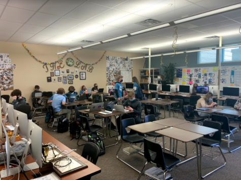 """Students sit in a half-empty classroom after returning to a full in-person schedule. Students returned March 22, and the school has already experienced quarantining students. """"It seems like every time I come to class more and more people are online, Aiden Macarthur 23' said."""