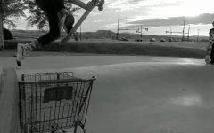 Kayden Ozdemir '24 jumping over a shopping cart at a local skate park.